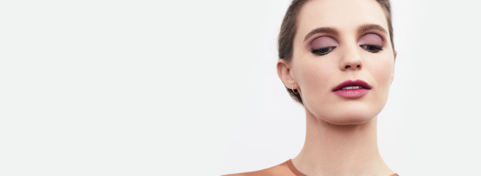 Get the step-by-step application tips for creating the season's on-trend Just-Bitten Lip Look from Mary Kay. A woman with brown hair is seen on the right side wearing pink and purple eye shadow with a light pink and purple lipstick.